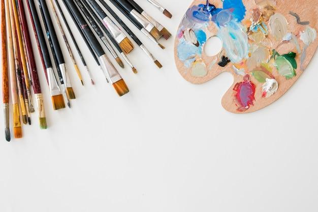Вид сверху набора кистей с палитрой краски и копией пространства
