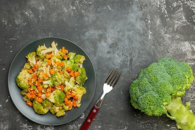 灰色の背景に茶色のボウルと新鮮な野菜のさまざまなスパイスのセットの上面図