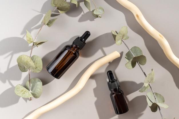 ユーカリの葉と木の棒で飾られた顔のエッセンシャルオイルのセットの上面図。ナチュラルスキンケア化粧品。