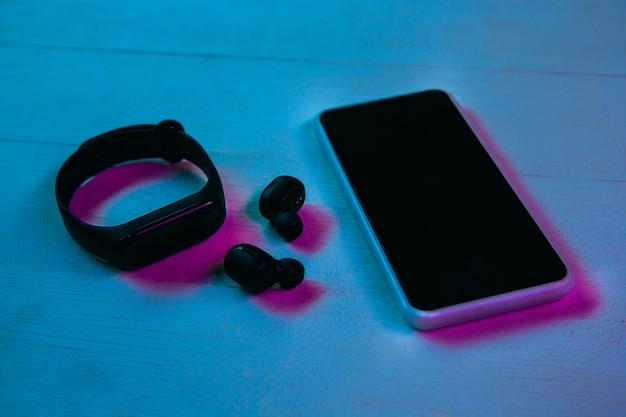 紫のネオンライトと青の背景のガジェットのセットの上面図。木製のテーブルにスマートフォン、スマートウォッチ、ワイヤレスヘッドフォン。広告用のコピースペース。テクノロジー、モダン、ガジェット。