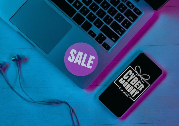 紫のネオンライト、青の背景のガジェットのセットの上面図。スマートフォン、スマートウォッチ、ラップトップ。テクノロジー、モダン、ガジェット、広告。ブラックフライデー、サイバーマンデー、販売、金融オンライン購入の概念