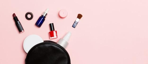 ピンクの化粧品バッグからこぼれるメイクアップとスキンケア製品のセットのトップビュー