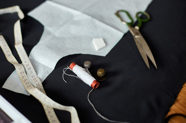 나무 테이블에 바느질 용품의 상위 뷰 : 바느질 실, 가위, 천 조각, 바늘, 센티미터, 패턴.