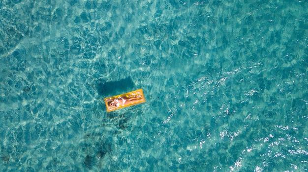 明るい晴れた夏の日に青いプールの水面の上の膨脹可能なベッドに横たわっている間、彼女の手でハートのシンボルを作るビキニのセクシーな女性の上面図。夏休みのプールの残りの概念
