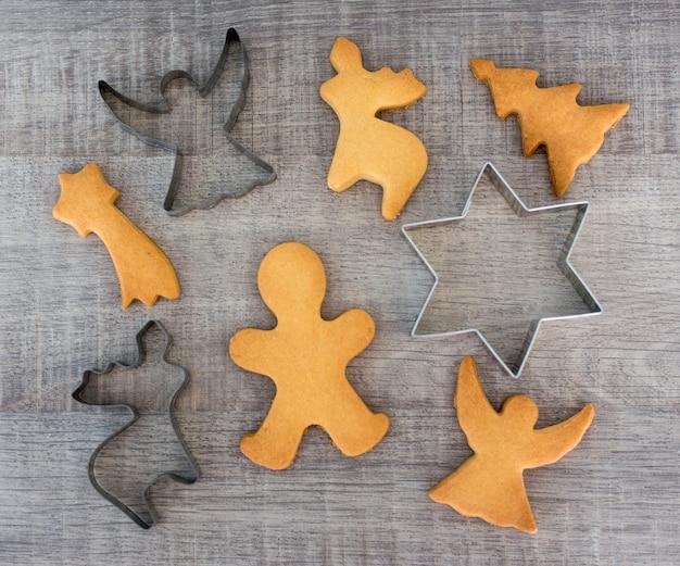 Вид сверху фигурного печенья или имбирных пряников и металлических резаков на деревянном столе