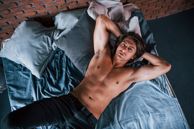 아침 시간에 침실에서 혼자 휴식을 취하는 벗은 섹시한 남자의 최고 전망.