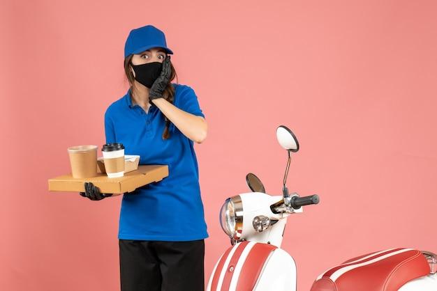 パステル ピーチ色の背景にコーヒーの小さなケーキを保持しているオートバイの隣に立っている医療マスク手袋を着てショックを受けた宅配便の女の子のトップ ビュー