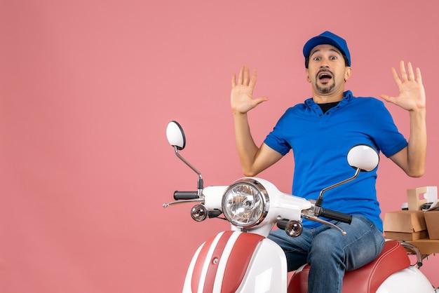 파스텔 복숭아 배경에 주문을 전달하는 스쿠터에 앉아 모자를 쓰고 충격을받은 택배 남자의 상위 뷰