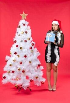 Вид сверху потрясенной девушки в черном платье в шляпе санта-клауса, стоящей возле рождественской елки и держащей новогодний подарок на красном