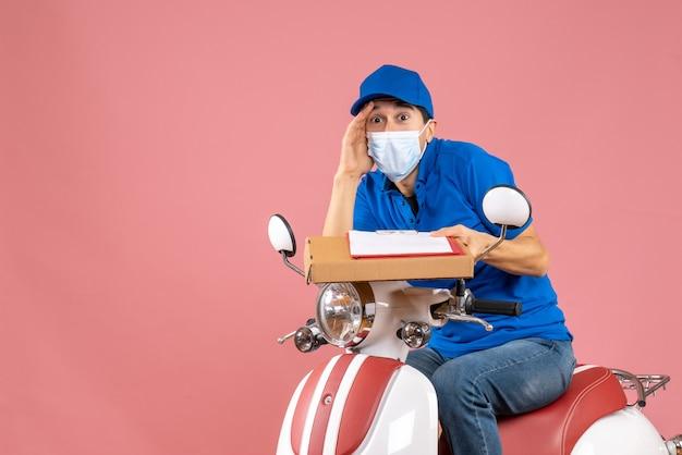 Вид сверху шокированного доставщика-мужчины в маске в шляпе, сидящего на скутере, доставляющего заказы, держа документ на персиковом фоне