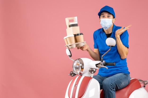 Вид сверху шокированного доставщика-мужчину в маске в шляпе, сидящего на скутере, доставляющего заказы на персике