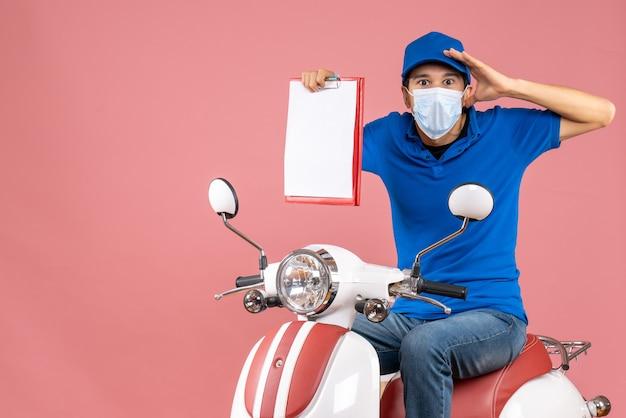 Вид сверху шокированного доставщика-мужчины в маске в шляпе, сидящего на скутере, показывая документ на пастельном персике