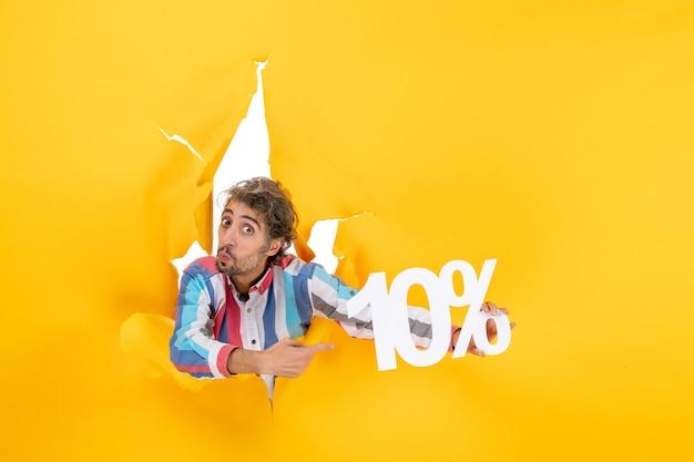黄色い紙の引き裂かれた穴に10パーセントを示すショックを受けた若い男の上面図