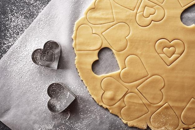 Вид сверху на песочное тесто с сердечками на сером фоне