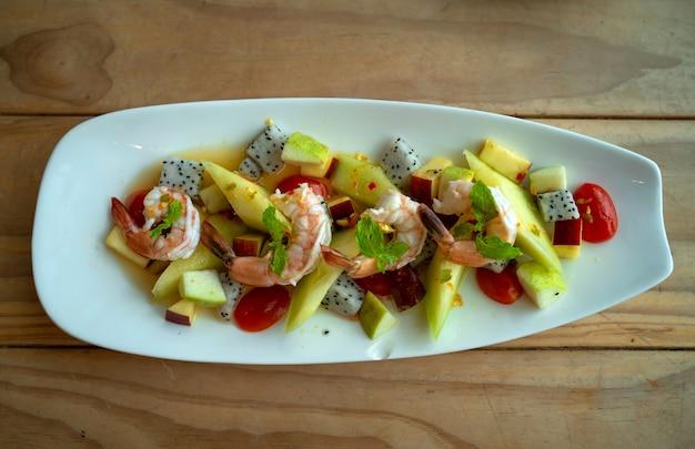 Вид сверху креветок с дыней и смешанными фруктами, острый салат в тайском стиле на деревянном столе, здоровая чистая еда