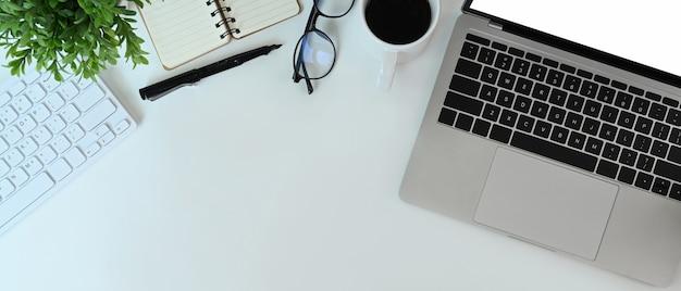 Вид сверху простого рабочего пространства с портативным компьютером, очками, ноутбуком, кофейной чашкой и заводом на белом столе.