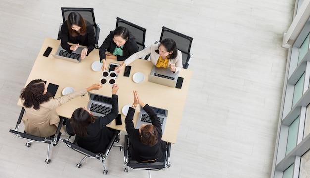木製の会議テーブルの周りに一緒に座って、オフィスのテーブルにラップトップやタブレットと一緒にコーヒーマグを応援し、チャリンという音を立てる6人のビジネスウーマンの上面図。ビジネス会議のコンセプト。