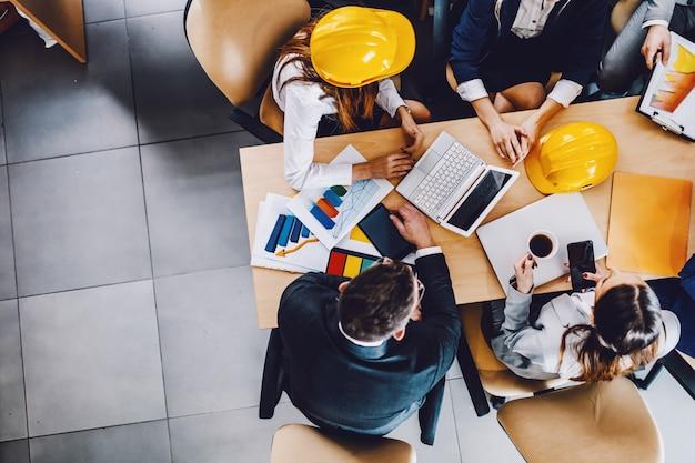 会議室のテーブルに座って、重要なプロジェクトについて会議を行っている6人の熱心な建築家の平面図。