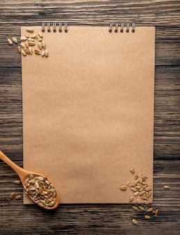 素朴なスケッチブックとヒマワリの種で木のスプーンのトップビュー