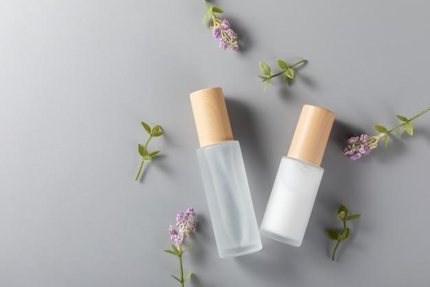 Вид сверху бутылочек для ухода за кожей на поверхности с цветком лаванды