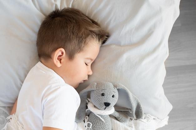 잠자는 소년의 최고 전망은 손에 토끼 장난감을 들고 침대에 누워 있습니다. 고품질 사진