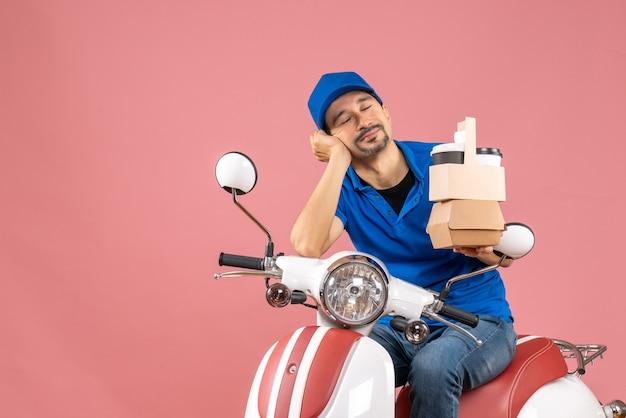 Вид сверху сонного курьера в шляпе, сидящего на скутере и показывающего заказы на пастельных персиках