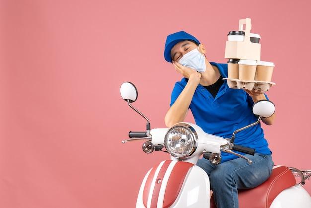 Вид сверху на сонного доставщика-мужчину в маске в шляпе, сидящего на скутере, доставляющего заказы на персике
