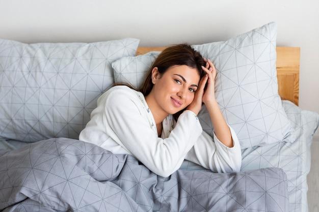 Вид сверху сонной женщины в постели в пижаме