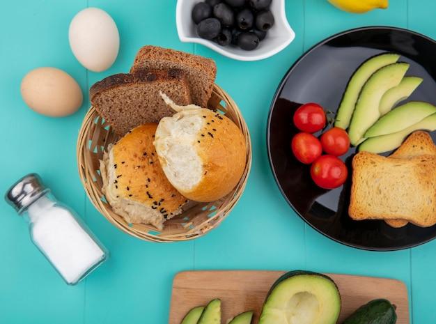 トマトと黒皿にスライスしたアボカドと青の表面に黒オリーブとパンのバケツとトーストしたパンのトップビュー