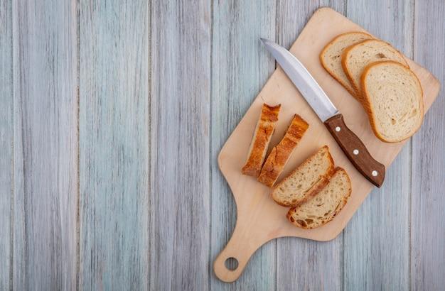 コピースペースを持つ木製の背景にまな板の上のスライスしたバゲットとナイフのトップビュー