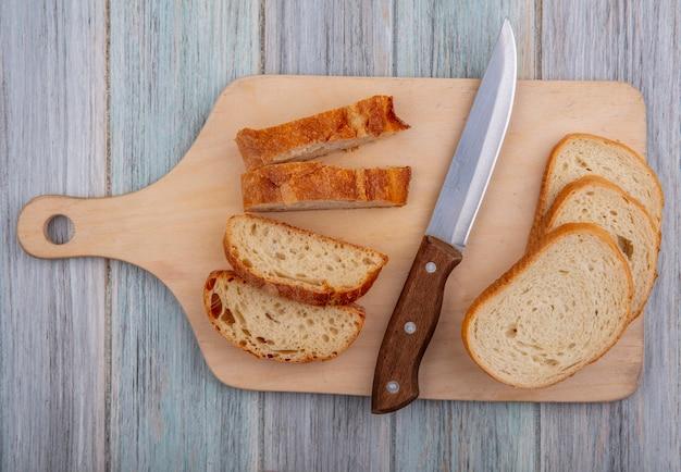 木製の背景にまな板の上のスライスバゲットとナイフのトップビュー