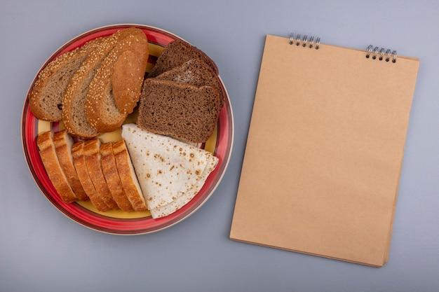 Вид сверху нарезанный хлеб в виде хрустящих лепешек из коричневых початков с семенами и ржаных в тарелке с блокнотом на сером фоне с копией пространства