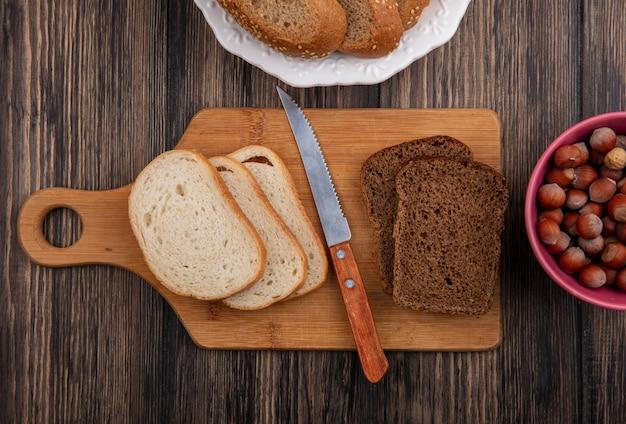 시드 브라운 옥수수 호밀과 격자 무늬 천으로 접시에 흰색과 칼과 나무 배경에 견과류 그릇으로 커팅 보드에 얇게 썬 빵의 상위 뷰