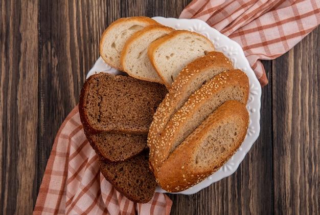 Вид сверху на нарезанный хлеб в виде засеянной коричневой ржи и белого хлеба в тарелке на клетчатой ткани на деревянном фоне