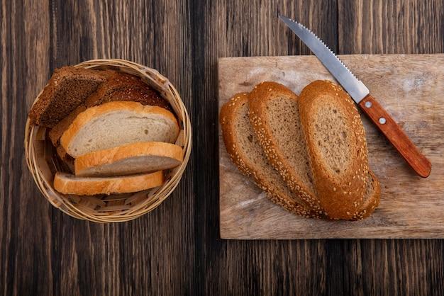 木製の背景にまな板の上のナイフでスライスされた茶色のパンの種まきとバスケットのライ麦白のものの平面図