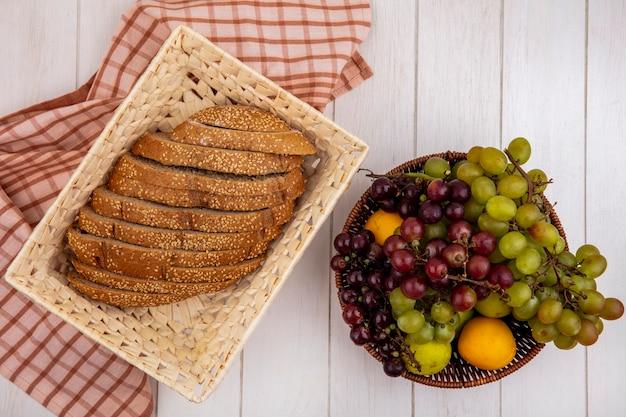 Вид сверху нарезанного коричневого початка с семенами в корзине на клетчатой ткани и корзине с фруктами в виде виноградного нектакота на деревянном фоне