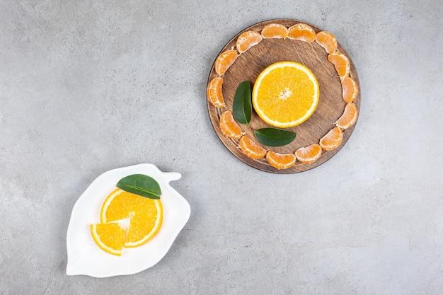 Вид сверху нарезанных цитрусовых. дольки мандарина и апельсина.