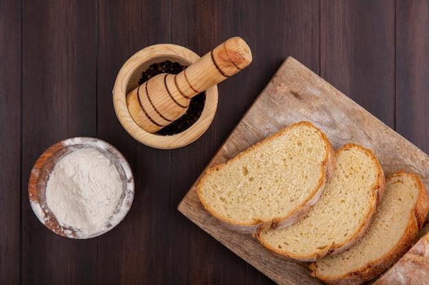 Вид сверху нарезанного хрустящего хлеба на разделочной доске и муки в миске с черным перцем в чесночной дробилке на деревянном фоне