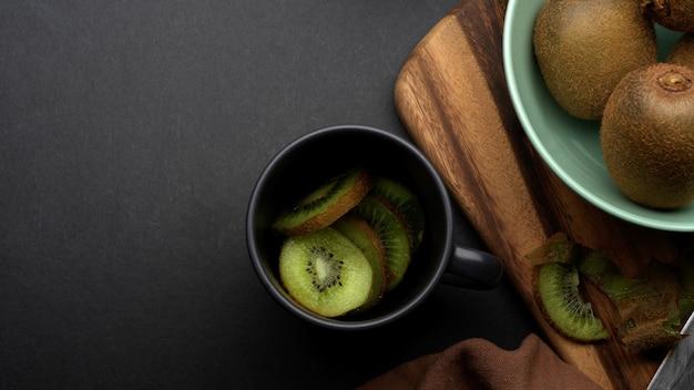 ボウルにキウイフルーツ全体とキッチンテーブルのセラミックカップでスライスした新鮮なキウイフルーツの上面図