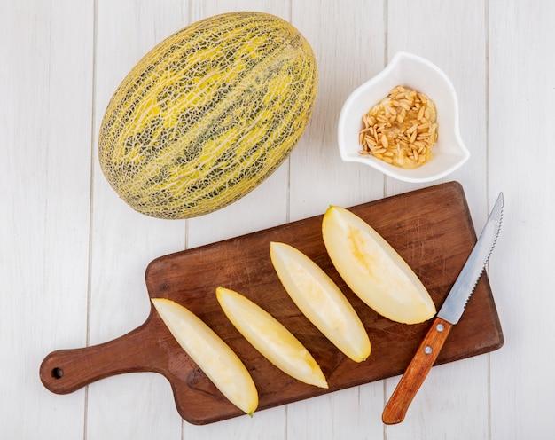 白い木製の表面に白いボウルに種子とナイフで木製キッチンボードにスライスした新鮮なメロンのトップビュー