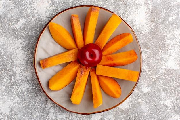 Вид сверху нарезанных свежих персиков внутри тарелки на светлой белой поверхности