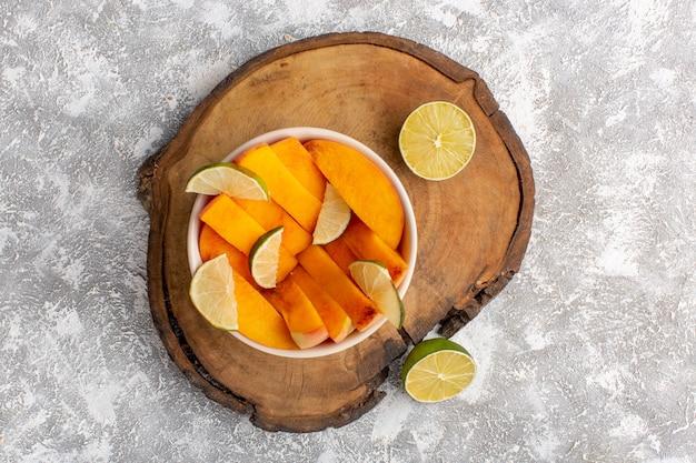薄白の表面にレモンとプレート内のスライスされた新鮮な桃の上面図