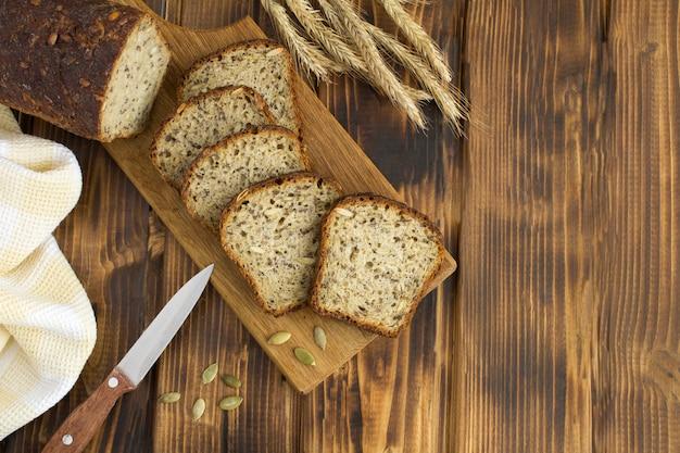 Вид сверху нарезанный домашний хлеб на разделочной доске на деревянном столе