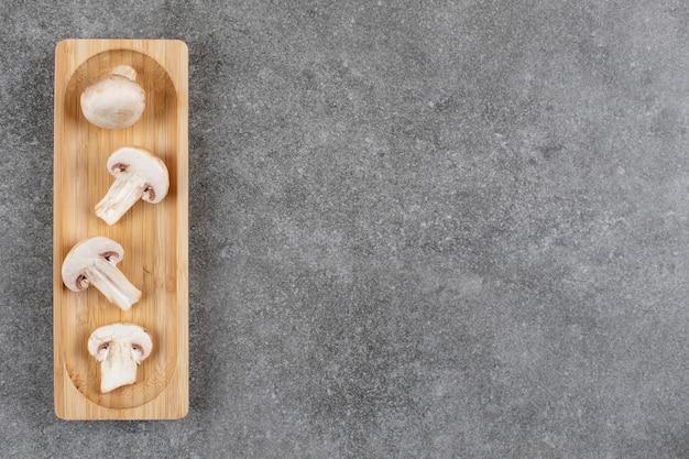 Вид сверху нарезанных грибов на деревянной доске над серым столом.