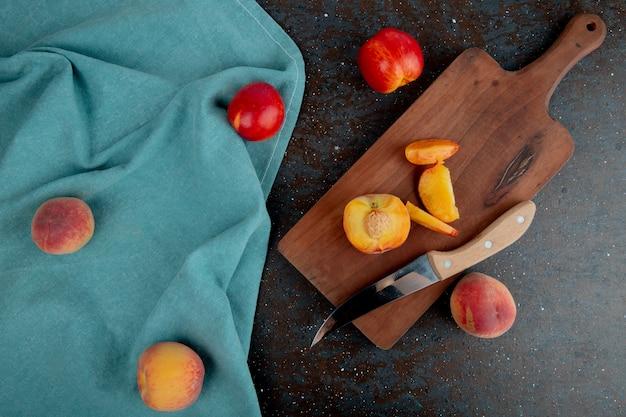 Взгляд сверху отрезанного персика с ножом на разделочной доске с всеми персиками на ткани на коричневой и черной поверхности