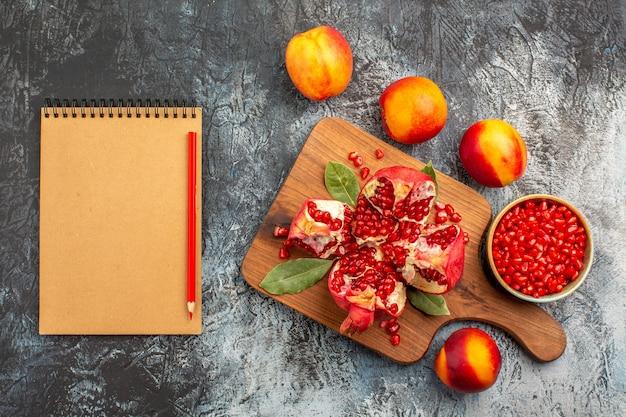 暗い床に桃とスライスしたザクロの上面図