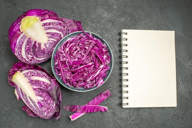 暗い背景にスライスした赤キャベツの新鮮な野菜の上面図