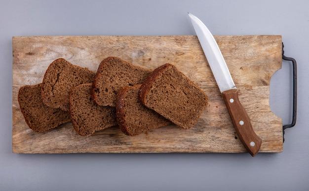 Вид сверху нарезанного ржаного хлеба и ножа на разделочной доске на сером фоне