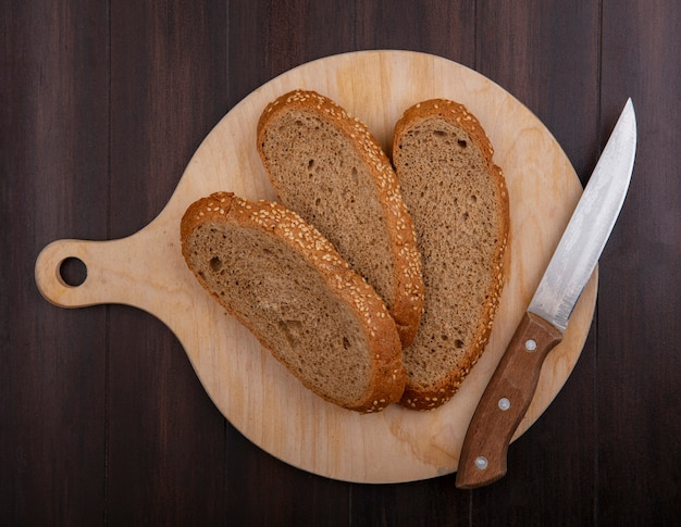 木製の背景にまな板の上のナイフでスライスされたシードの茶色の穂軸のトップビュー