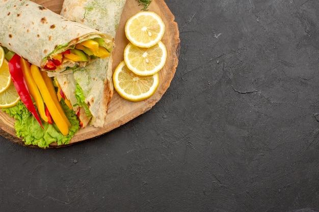黒のテーブルにレモンスライスとスライスしたシャワルマのおいしい肉サンドイッチの上面図